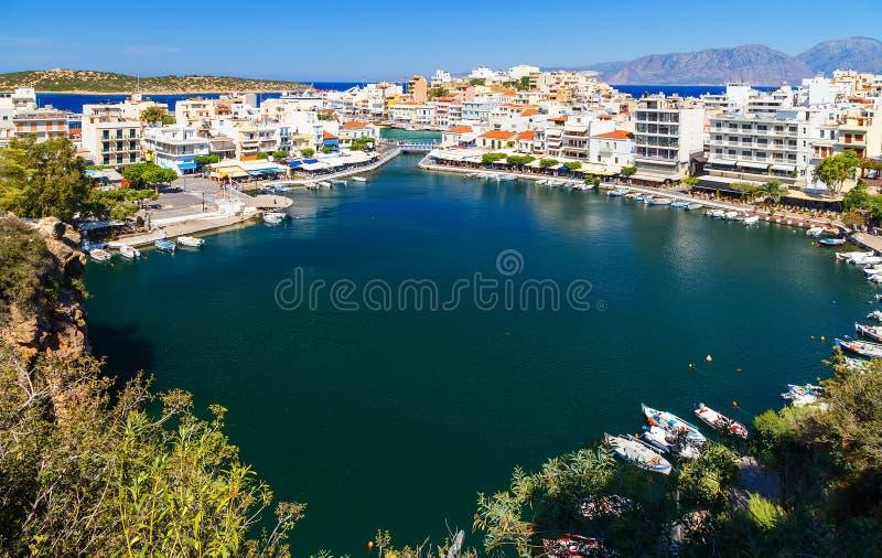 贴水帕帕佐普洛斯或Ayios, Aghios镇全景在克利特,希腊 显示著名地方:湖,小游艇船坞,海湾,老镇 库存照片