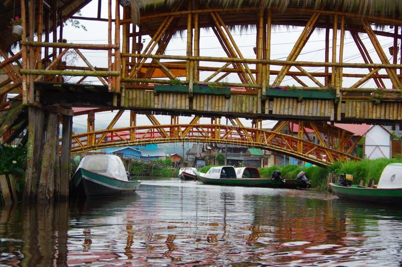 帕斯托,哥伦比亚- 2016年7月3日:一些绿色小船停放了在两座桥梁以下在接近la cocha湖的一条河 免版税图库摄影