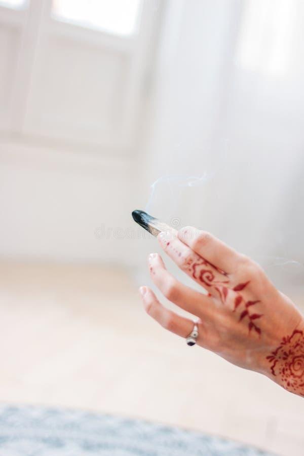 帕洛santo或Bursera graveolens 停滞熏制的圣洁木头,关闭的白肤金发的年轻女人 免版税图库摄影