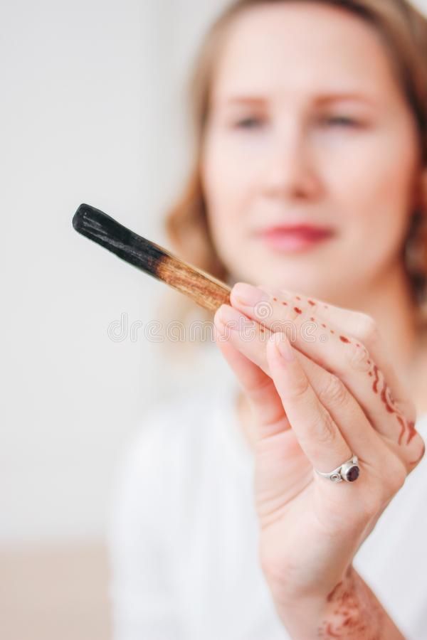 帕洛santo或Bursera graveolens 白肤金发的年轻女人藏品棍子圣洁木头,关闭 库存照片