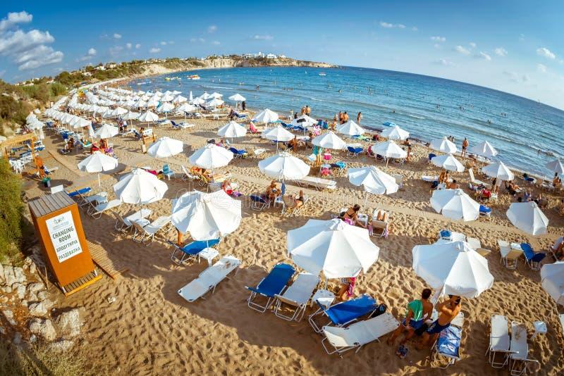 帕福斯,塞浦路斯- 2017年8月20日:海滩休息室和阳伞行在一个珊瑚湾海滩在Peyia村庄附近 免版税库存图片
