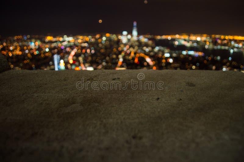 从帝国大厦观察台看见的曼哈顿,街市和世界贸易中心一号大楼模糊的光在晚上 图库摄影