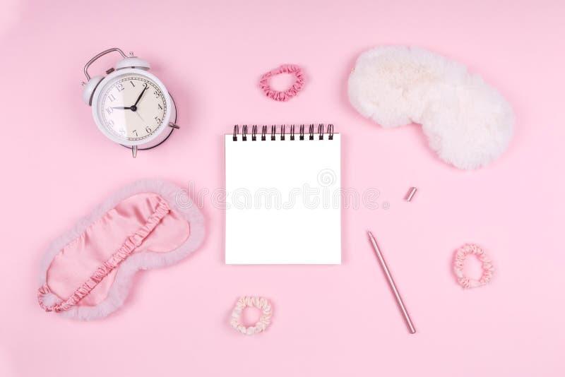 带可爱蓬松的睡眠面罩和粉色附件的记事本 免版税库存照片