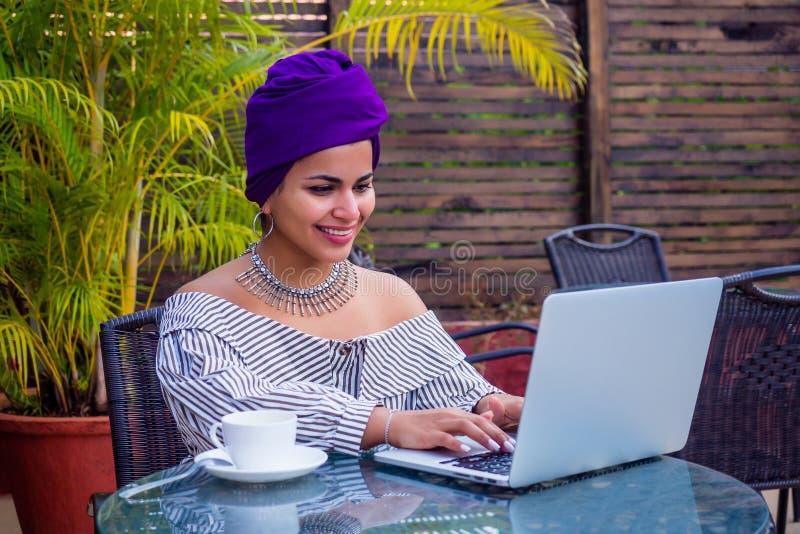 带头文化的印度美女微笑着在户外夏日咖啡馆在笔记本电脑上工作 免版税库存照片