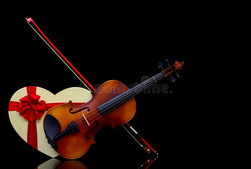 带弓和深色背景中心形礼盒的古典小提琴 库存照片