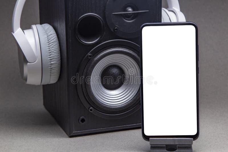 带智能手机模型的白色耳机,在灰色音乐上隔离在线概念 免版税库存图片