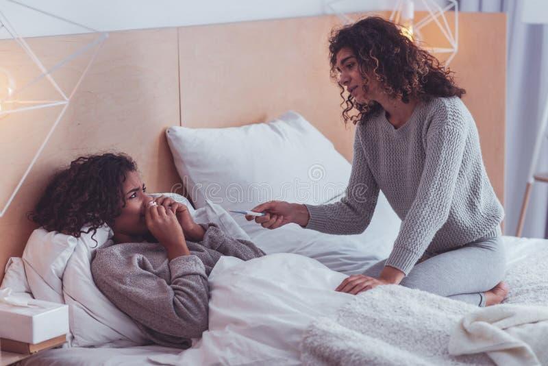 带来温度计的有同情心的女孩给她病的表兄弟 库存照片