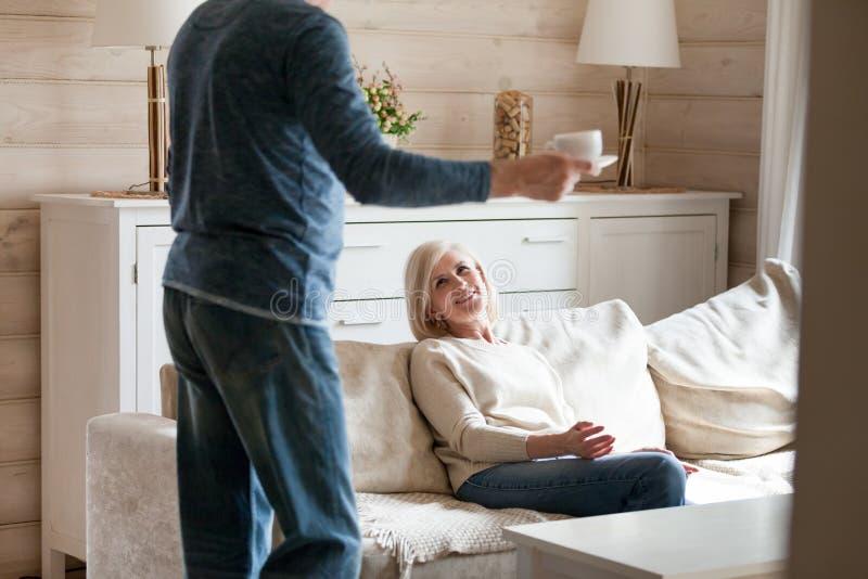 带来茶的爱的年迈的丈夫给微笑的妻子 库存照片