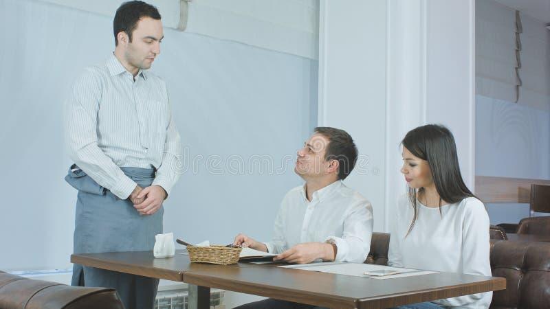 带来菜单的侍者给坐在桌上的年轻夫妇在餐馆 免版税库存照片