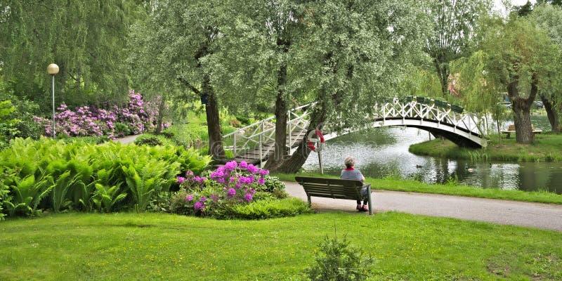 带池塘、鲜花、长凳和桥的公园的户外景观 免版税库存图片