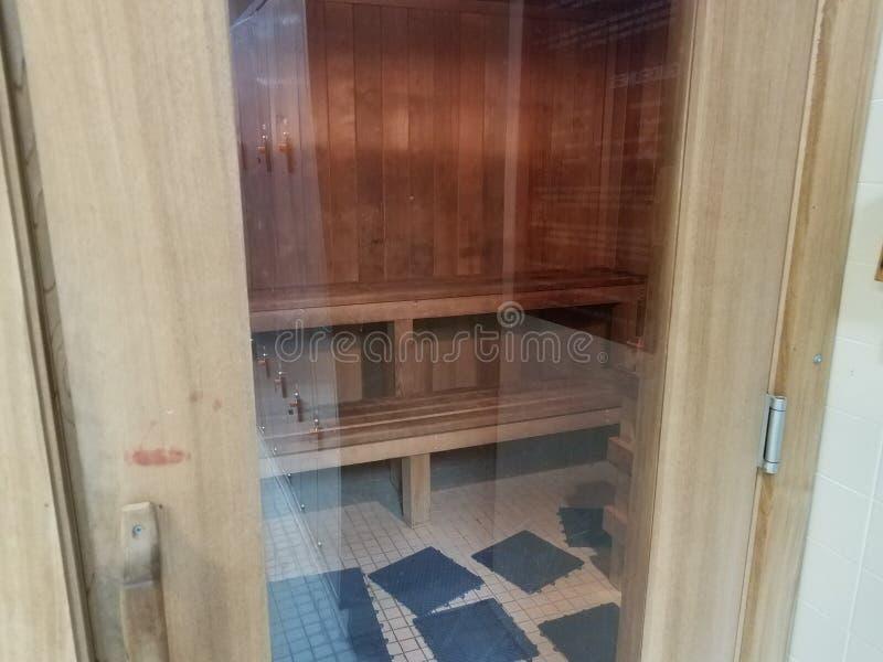 带玻璃门和木凳的木桑拿房 免版税库存照片