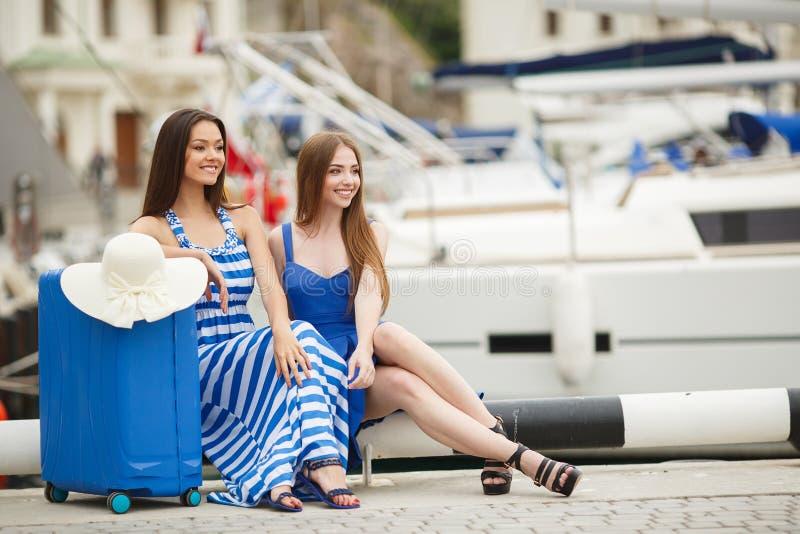 带着一个手提箱的两个女孩在小游艇船坞 免版税库存图片