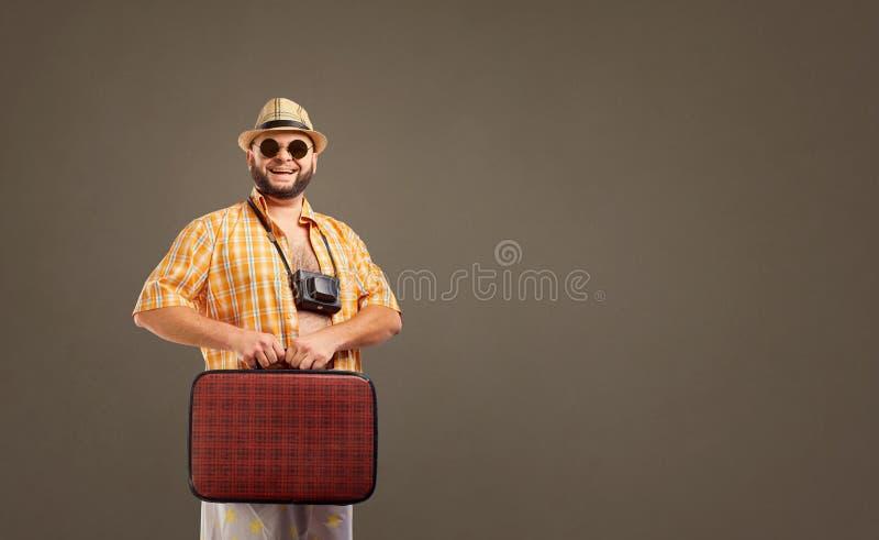 带着一个手提箱的滑稽的肥胖有胡子的人在度假 免版税库存图片