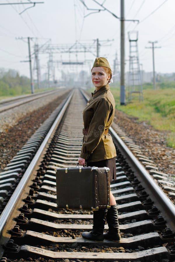 带着一个手提箱的苏联女兵在站立在火车轨道的第二次世界大战的制服 免版税库存照片