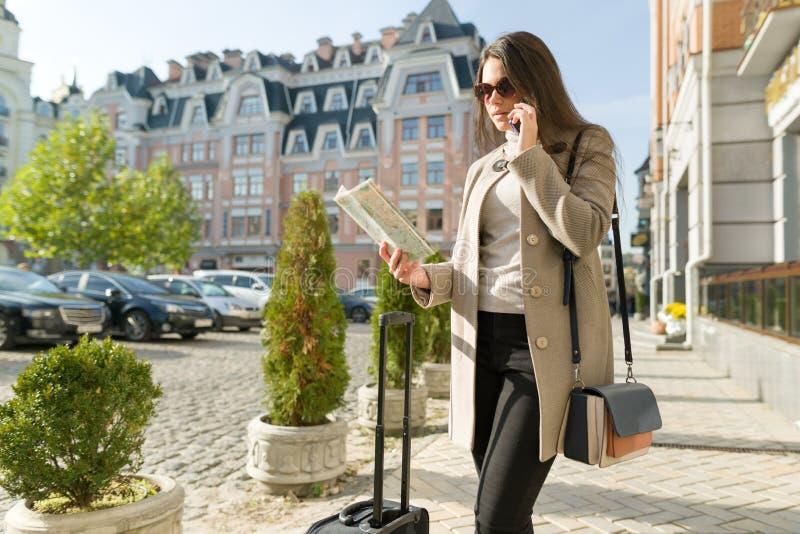 带着一个旅行手提箱的年轻美丽的女商人在晴朗的城市街道上,有旅游地图的女孩谈话在手机 库存照片