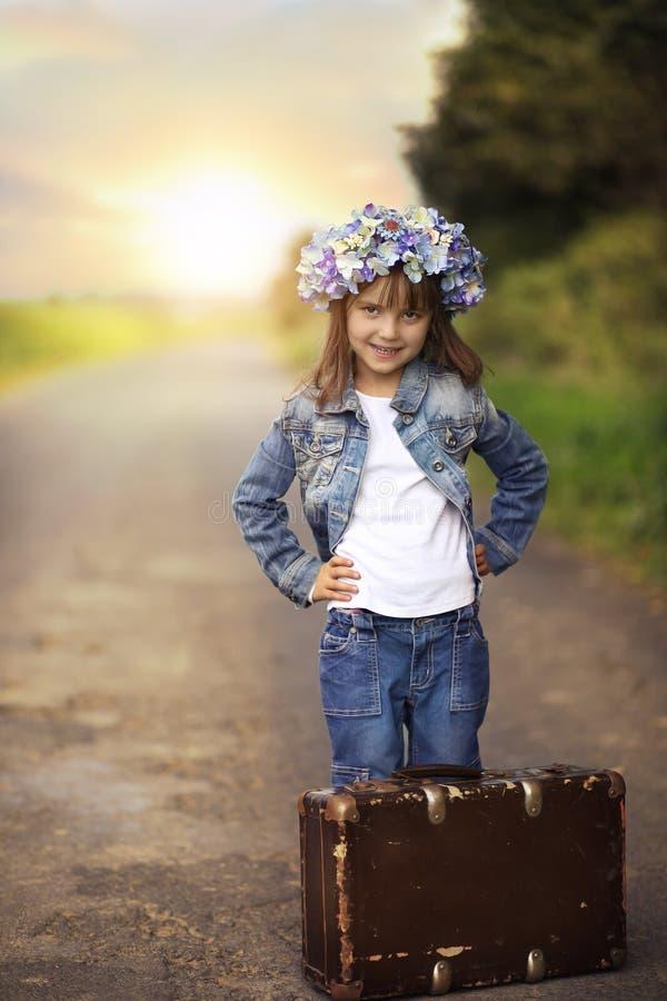 带着一个老手提箱的一个小女孩 免版税库存照片