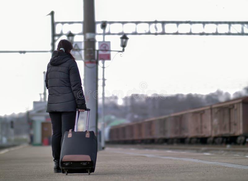 带着一个黑手提箱的一个孤独的女孩在等待火车的平台站立 库存图片