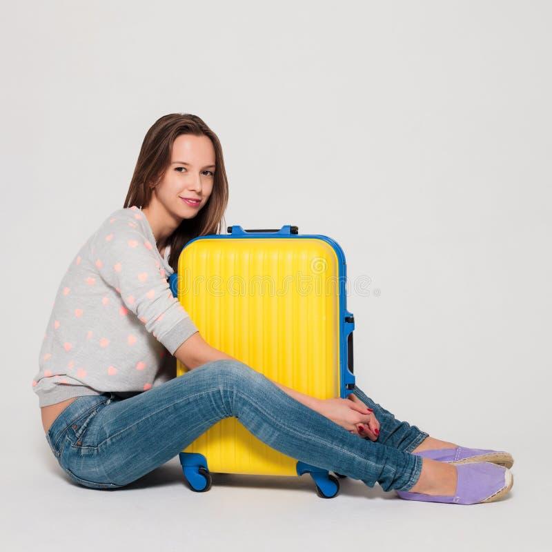 带着一个黄色手提箱的女孩 库存照片