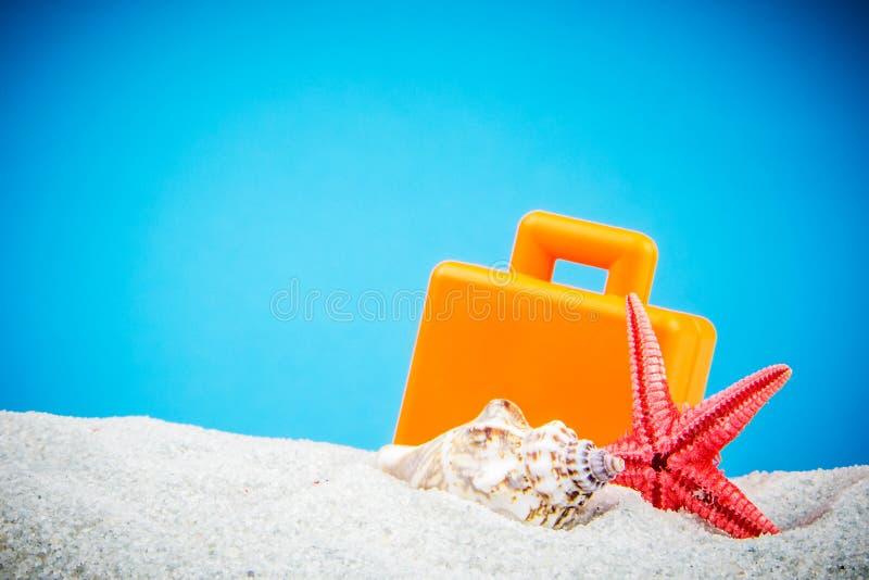 带着壳和手提箱的沙子海滩 图库摄影