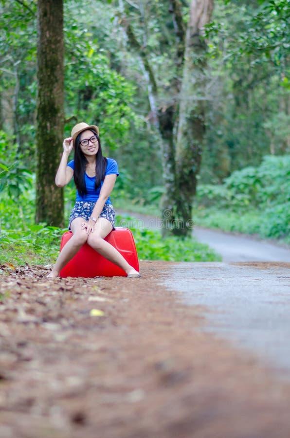 带着大红色手提箱的滑稽的小女孩在路 她等待的公共汽车和愉快关于旅行 库存照片