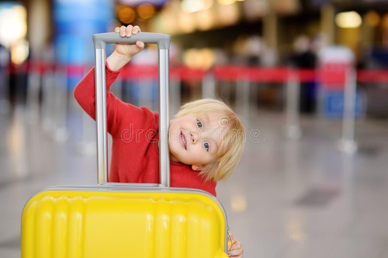 带着大黄色手提箱的逗人喜爱的愉快的小男孩在飞行前的国际机场 免版税库存图片