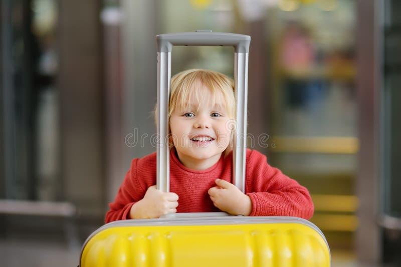 带着大黄色手提箱的逗人喜爱的愉快的小男孩在飞行前的国际机场 库存照片
