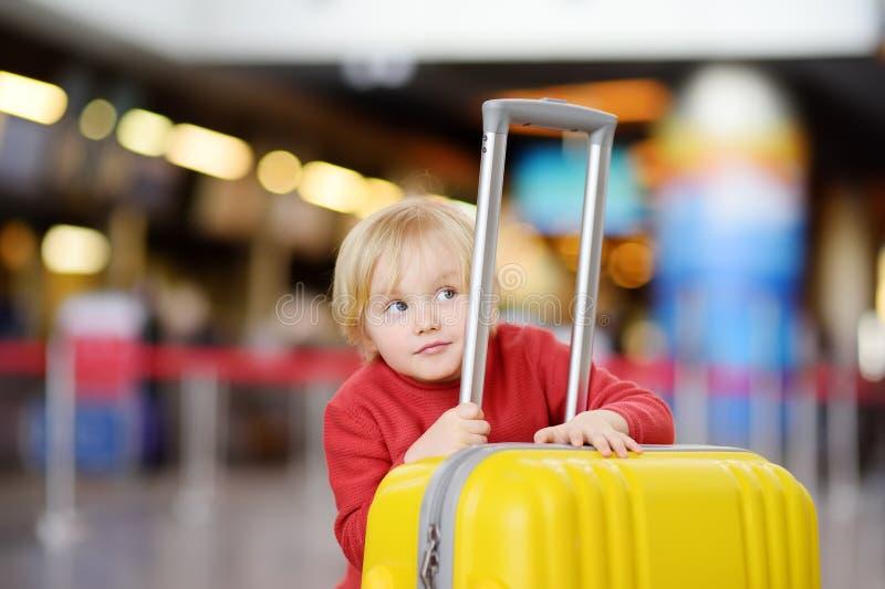 带着大黄色手提箱的逗人喜爱的愉快的小男孩在飞行前的国际机场 库存图片
