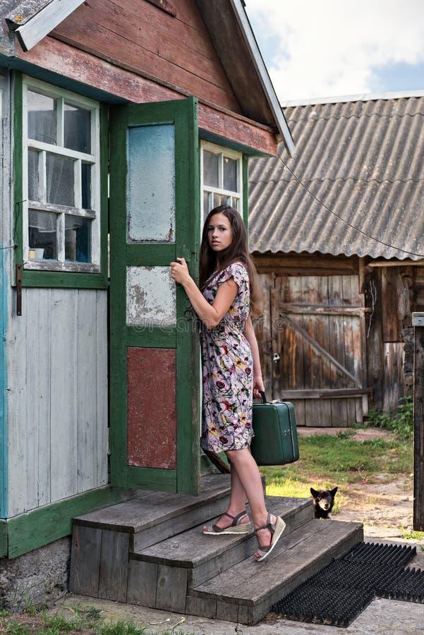 带着手提箱的一位农村年轻老师通过一所老,破旧的村庄学校的门走在乡下 库存照片