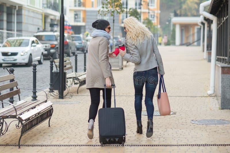 带着手提箱的两名年轻微笑的妇女走沿城市街道的 都市背景,秋天天,从后面的看法 免版税库存照片