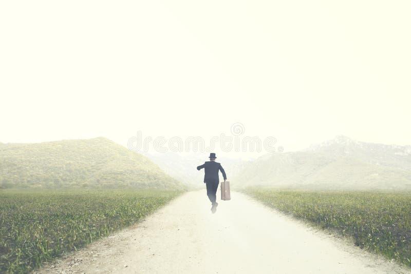 带着手提箱的人在一条离开的路快速地跑到一个未知的目的地 免版税图库摄影