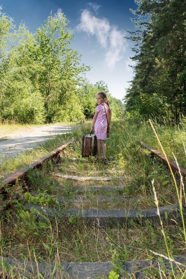 带着手提箱的女孩在铁路 免版税库存图片