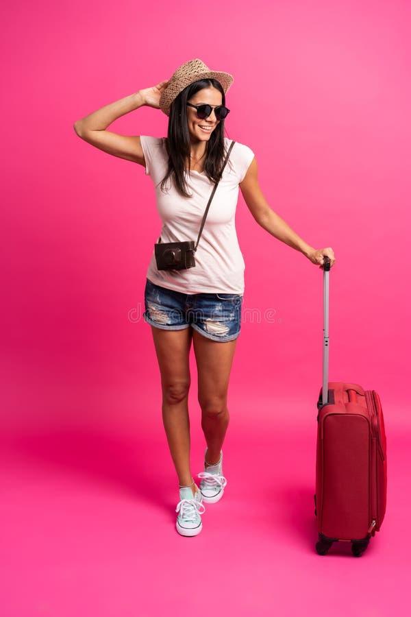 带着手提箱的妇女旅客在颜色背景 库存图片