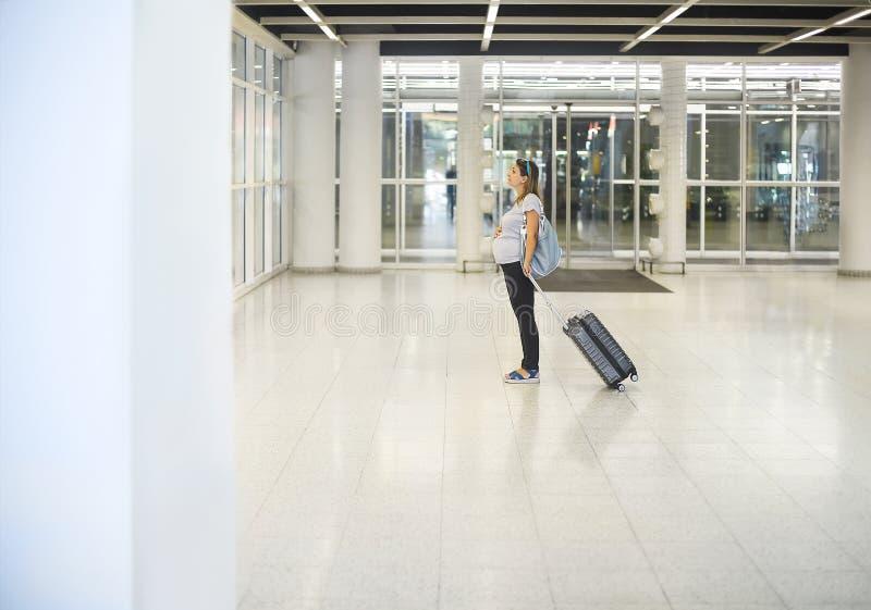 带着手提箱的孕妇在机场或驻地 免版税图库摄影