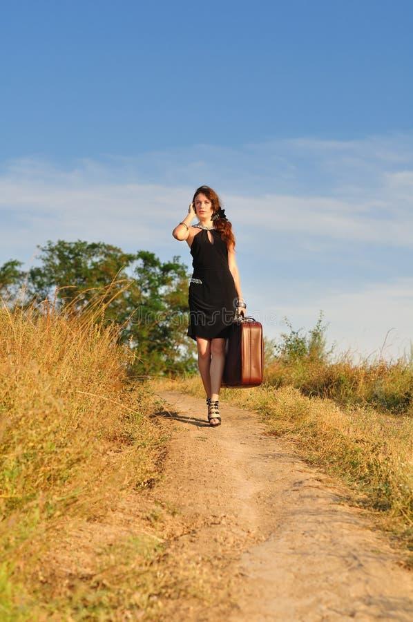 带着手提箱的孤独的女孩在乡下公路 免版税库存图片