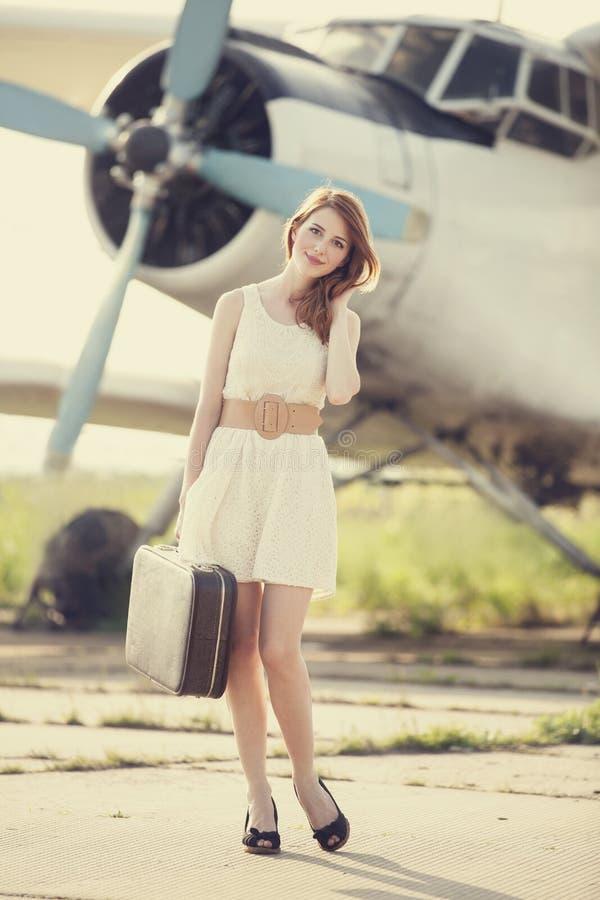 带着手提箱的孤独的女孩在近的飞机。 免版税库存照片