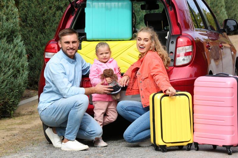 带着手提箱的年轻家庭临近车厢 库存照片