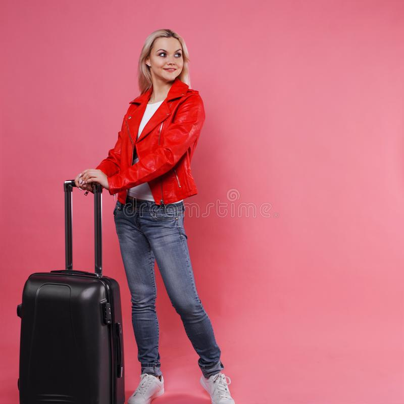 带着手提箱的年轻美丽的白肤金发的妇女在桃红色背景 库存图片