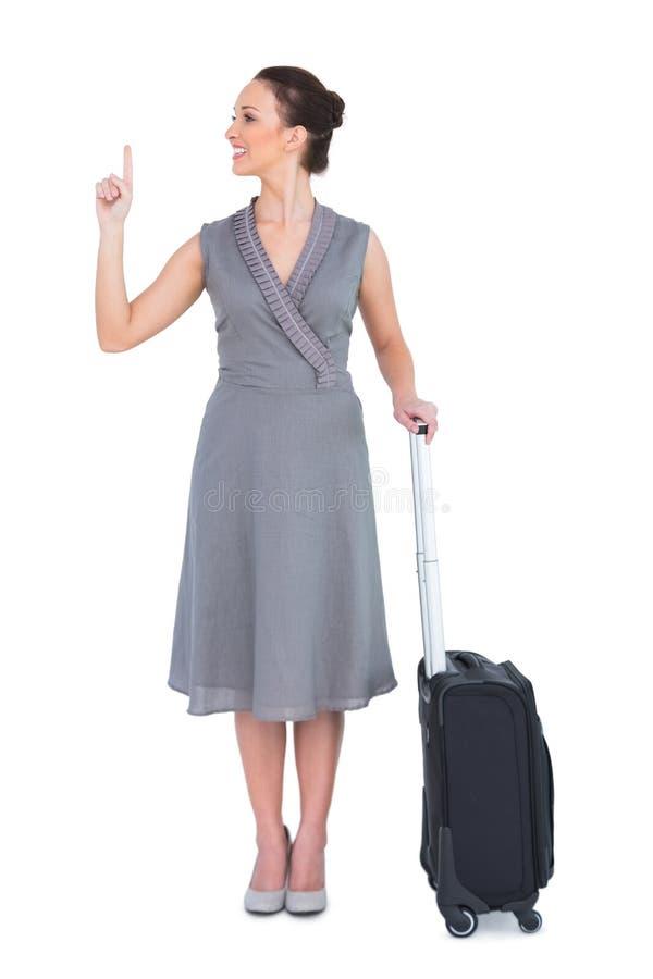 带着手提箱的快乐的华美的妇女指向她的手指的  免版税库存照片