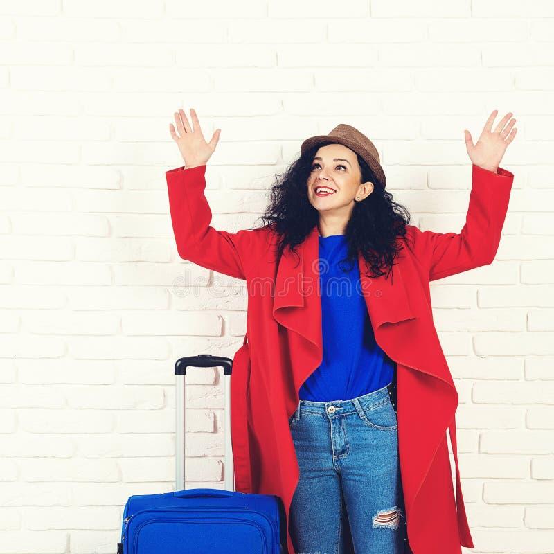 带着手提箱的愉快的旅行女孩 在红色外套和帽子打扮的激动的年轻女人 时兴的女孩准备好旅行 蓝色手提箱 免版税库存图片