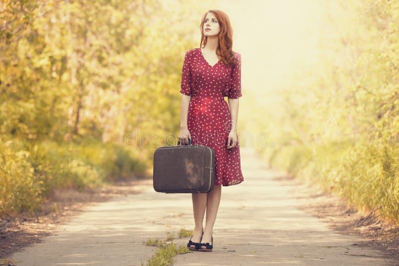 带着手提箱的红头发人女孩 库存照片