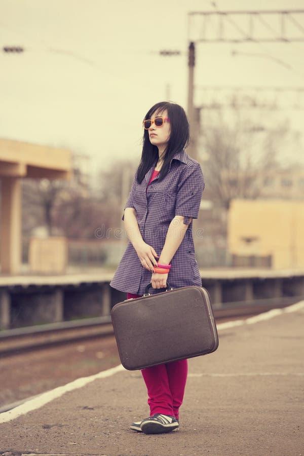 带着手提箱的年轻时尚女孩在铁路。 库存照片