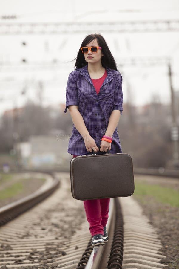 带着手提箱的年轻时尚女孩在铁路。 免版税库存照片