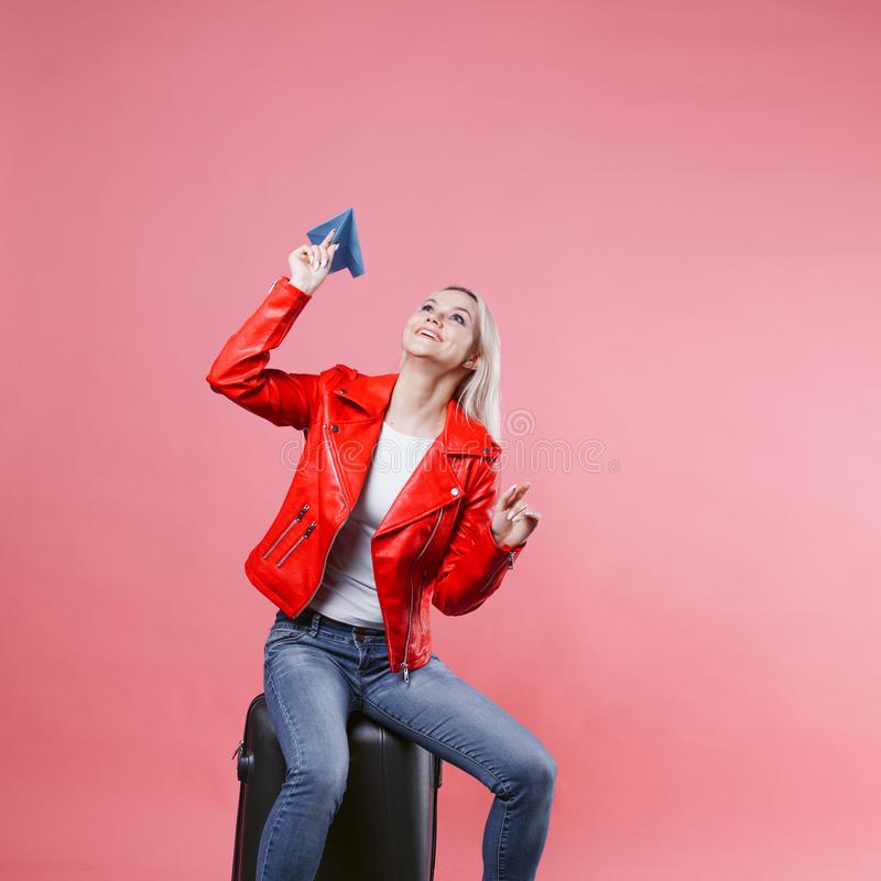 带着旅行手提箱的愉快的少妇发射纸飞机 桃红色背景的,概念白肤金发的旅游女孩 免版税库存图片