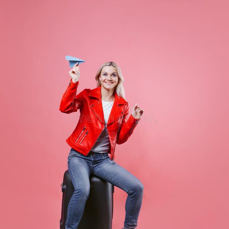 带着旅行手提箱的愉快的少妇发射纸飞机 桃红色背景的,概念白肤金发的旅游女孩 免版税库存照片