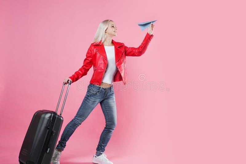 带着旅行手提箱的愉快的少妇发射纸飞机 桃红色背景的,概念白肤金发的旅游女孩 库存图片