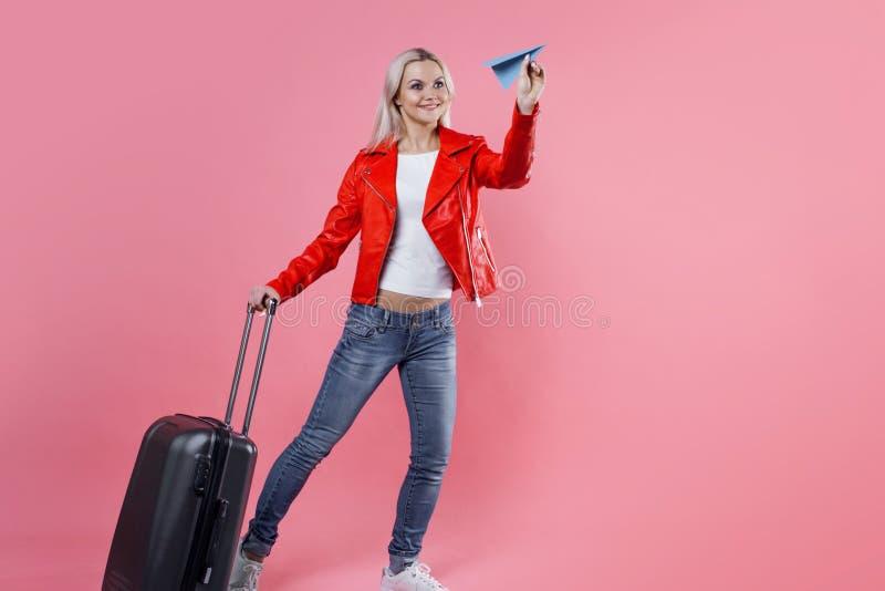 带着旅行手提箱的愉快的少妇发射纸飞机 桃红色背景的,概念白肤金发的旅游女孩 图库摄影