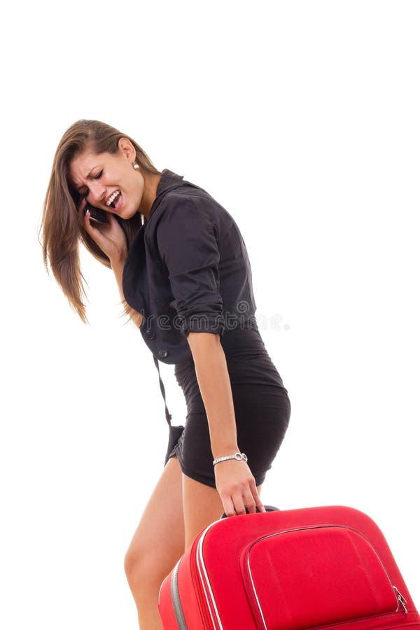 带着旅行手提箱的生气女商人 库存图片