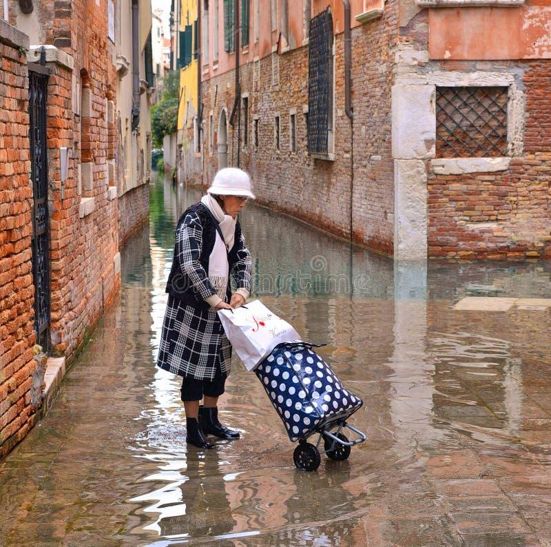 带着松紧鞋、起动和手提箱的Trandy时兴的成熟妇女在老狭窄的被充斥的街道的大浪 图库摄影
