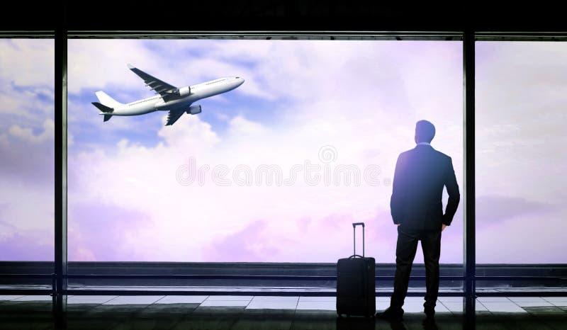 带着看机场窗口的手提箱的人,当等待飞行离开时 库存图片