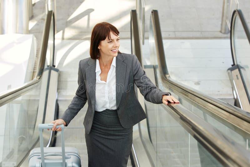 带着站立在自动扶梯的手提箱的微笑的女商人 免版税库存图片